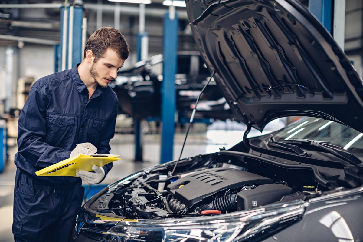 Man with clipboard checking under hood of car