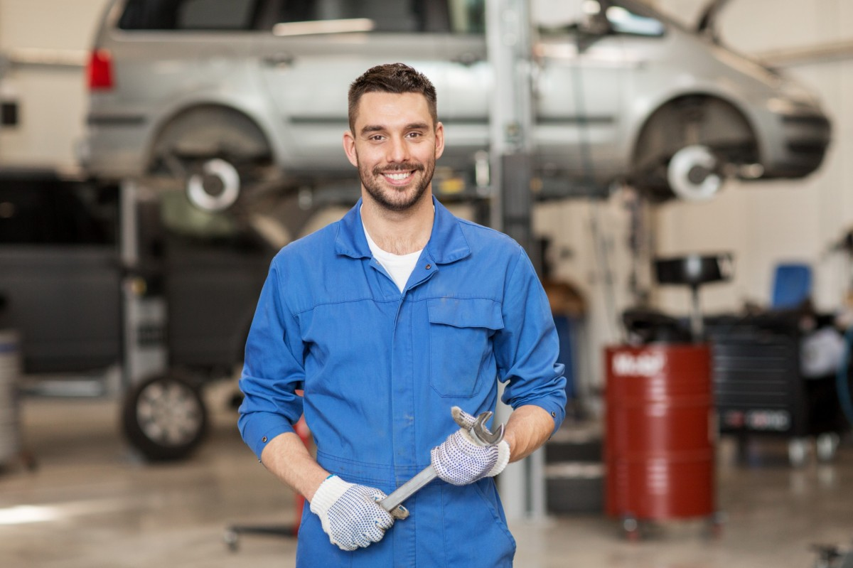 mechanic standing in garage and holding wrench